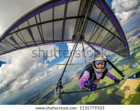 Smiling girl hang glider pilot shows thumb up while flying high over green fields below clouds. Wide angle selfie photo of extreme sport taken with action camera Сток-фото ©