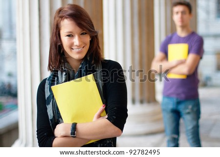 Smiling girl holding a notebook with a boy at the background