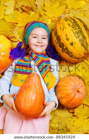 Smiling girl holding pumpkin in hands