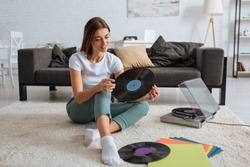 smiling girl holding vinyl record while chilling at home