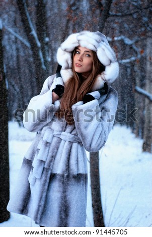 smiling girl in a fur coat in the winter forest under snowfall