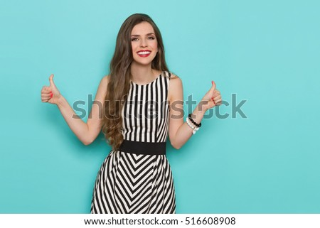 Smiling girl in black and white striped dress showing thumb up and looking at camera. Three quarter length studio shot on turquoise background.