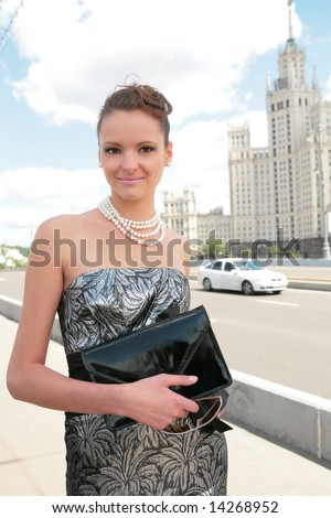smiling girl in black-silvery dress on background of the old moscow skyscraper