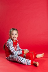 smiling girl in Christmas pajamas sits on the floor and holds a gift box with her feet, isolated on a vibrance background.