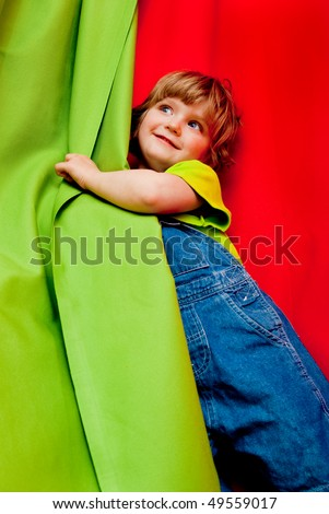 smiling girl in jeans between green and red curtains