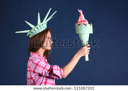 Smiling girl in pink shirt in crown holds and looks at torch - statue of liberty.