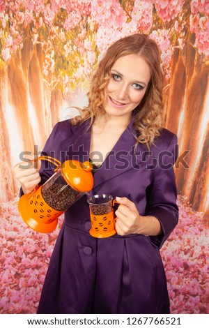 smiling girl in purple coat stands with orange French press and transparent Cup filled with coffee beans #1267766521