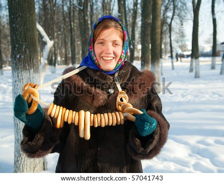 Smiling girl in russian traditional  clothes  with  round cracknel