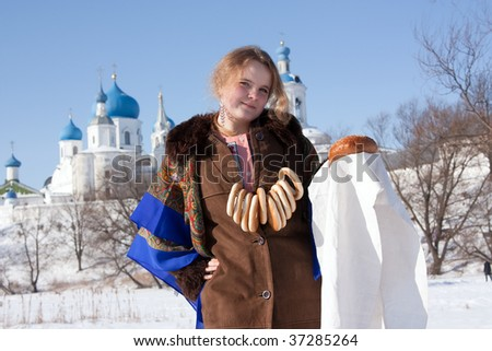 Smiling girl in russian traditional kerchief with round cracknel