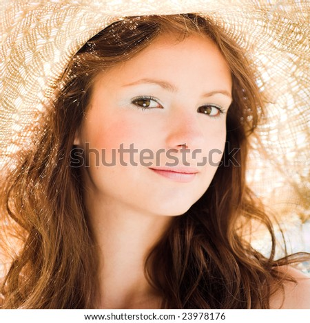 Smiling girl in straw hat portrait