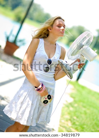 smiling girl in summer dress cooling herself with fan