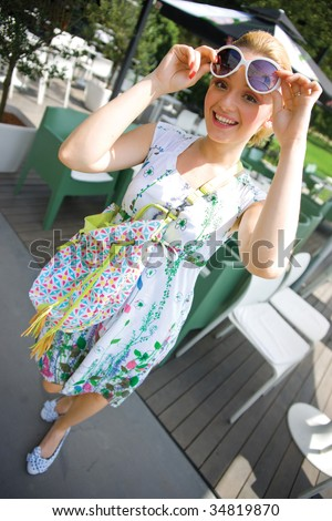 smiling girl in summer dress with bag on bar terace