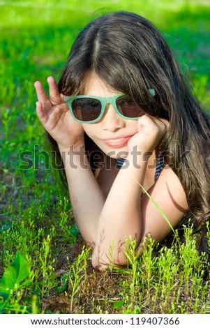 Smiling girl in sunglasses on green grass
