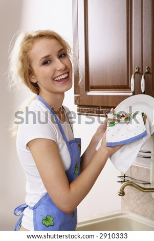 Smiling girl in the apron drying the dishes