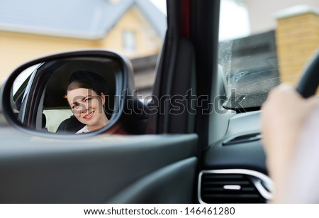 Smiling girl in the car looking in the mirror