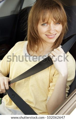 Smiling girl in the car putting on safety belt