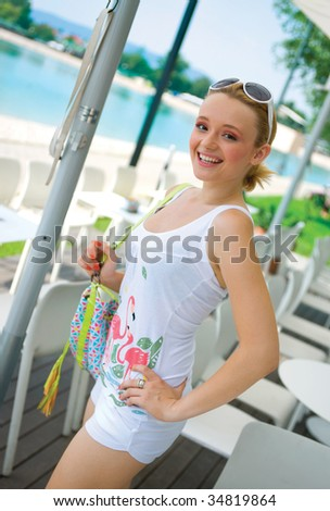 smiling girl in white summer clothes with bag