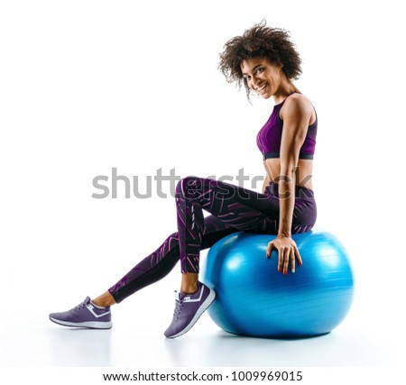 Stock Photo Smiling girl is resting sitting on gymnastic ball. Photo of sporty african girl in sportswear on white background. Sports