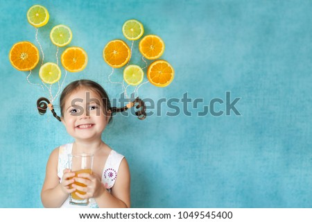 Smiling girl keeps glass of fresh citrus juice with bright balloons (orange and lemon slices) on her pigtails. Place for text