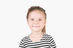 Smiling girl looking at camera. Smirking girl laughing inside and saying by her face I told you, I was right,  I knew it. Portrait of posing little girl wearing striped shirt. Isolated background.