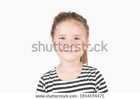 Smiling girl looking at camera. Smirking girl laughing inside and saying by her face I told you, I was right,  I knew it. Portrait of posing little girl wearing striped shirt. Isolated background. Foto stock ©