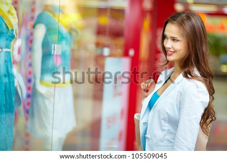 Smiling girl looking at the shop window before entering the store