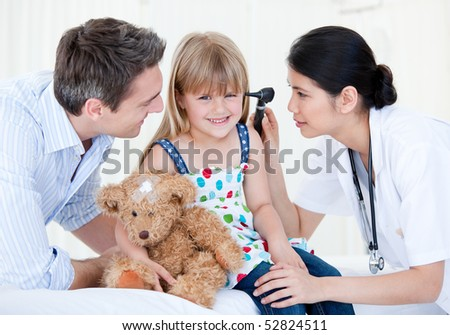 Smiling girl looks happy with her teddy bear against white background