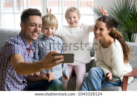 Smiling girl making mother and brother bunny ears while father taking happy family selfie, playful adopted children having fun posing for funny photo on smartphone with loving mom and dad together