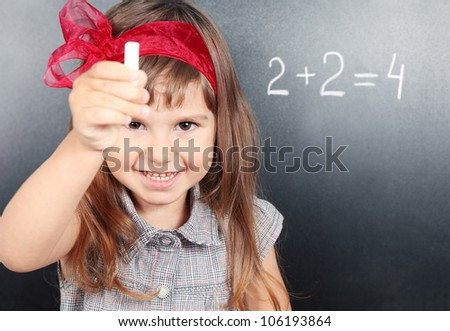 Smiling Girl Near Blackboard Showing Chalk Portrait