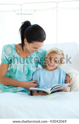 Smiling girl on a hospital bed reading with her mother