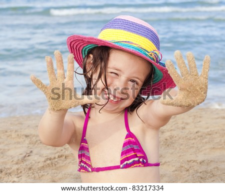 Smiling girl on the beach wearing colorful hat shows her sandy hands