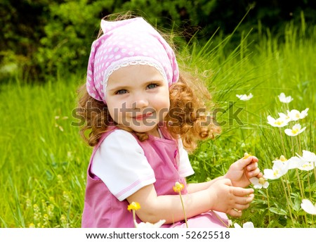Smiling girl  on the meadow looking right at camera