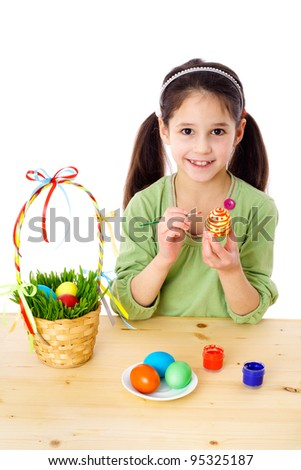 Smiling girl painting easter eggs, isolated on white
