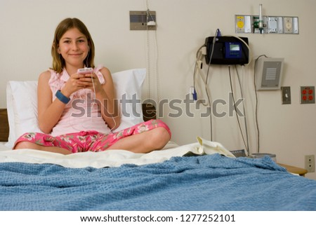 Smiling girl patient in hospital bed with MP3 player at camera