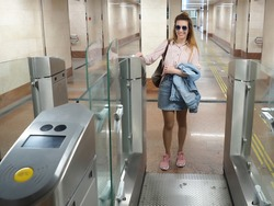 Smiling girl putting a ticket to the turnstile for the passage to the electric train