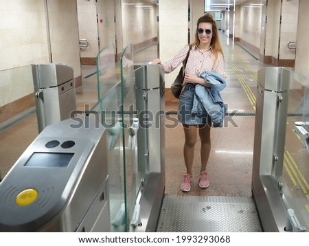 Smiling girl putting a ticket to the turnstile for the passage to the electric train Photo stock ©