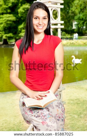 smiling girl reading outdoor in front lake in park