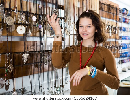 Smiling girl seller offering fashionable bracelets and pendants in the store #1556624189