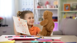 Smiling girl showing drawings teddy bear, playroom leisure, imaginary friend
