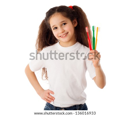 Smiling girl showing three toothbrushes, isolated on white