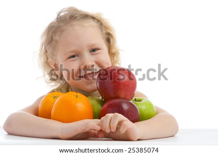 Smiling girl sits at the table with fruit heap