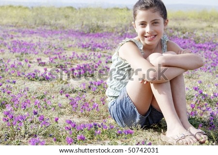 Smiling Girl sitting, arms around folded legs in Field of Flowers
