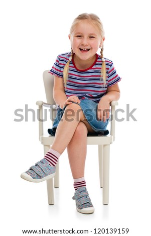 Smiling girl sitting on a chair. Studio shot.