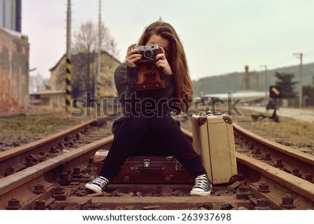 Stock Photo Smiling girl sitting on old suitcase on the track and also the old retro camera