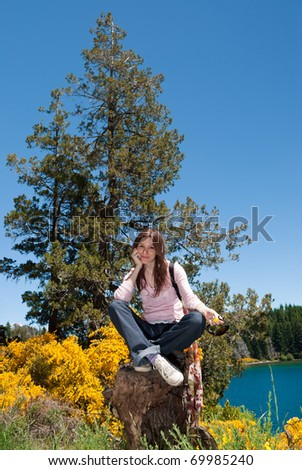 smiling girl sitting on tree trunk in the forest near a lake - stock photo
