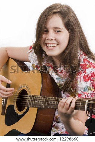 Smiling girl strumming an acoustic guitar isolated on white