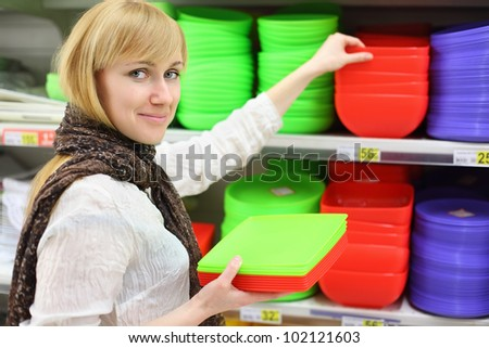 Smiling girl wearing scarf chooses colored plates in shop; shallow depth of field