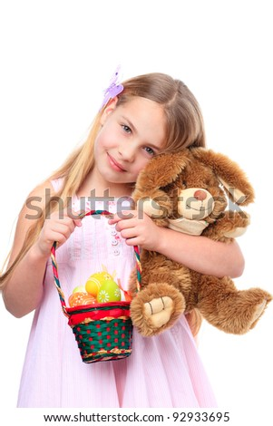 smiling girl with a basket filled with easter eggs cuddle with a bunny