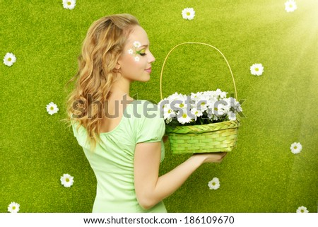 Smiling girl with a basket of flowers on a green background