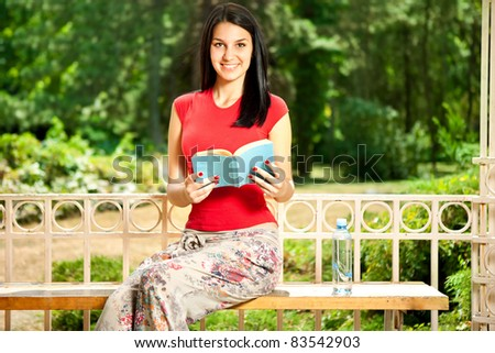 smiling girl with a book sitting on a bench in the park